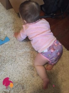Baby crawling away with cloth diaper on